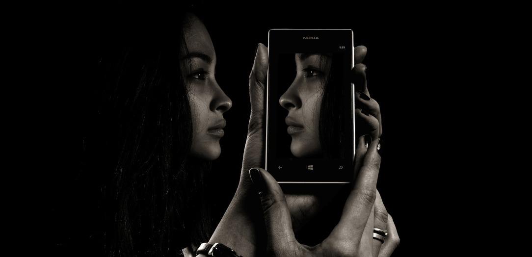 A face reflected in a smartphone